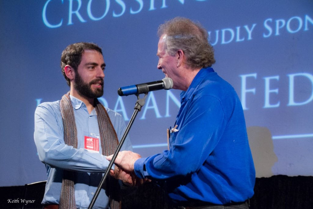 Flavio Villani, the subject of Crossing Rachmaninoff, clasps hands with host Spencer Brewer at the US premiere of the film, which received two standing ovations. Photo courtesy of Keith Wyner.